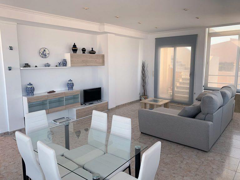 Proyecto 18381 desarrollado por CASANOVA en la Playa de Xeraco (Valencia): salón comedor, tapicería, mesa de centro, mesa, sillas, cortinas y decoración.