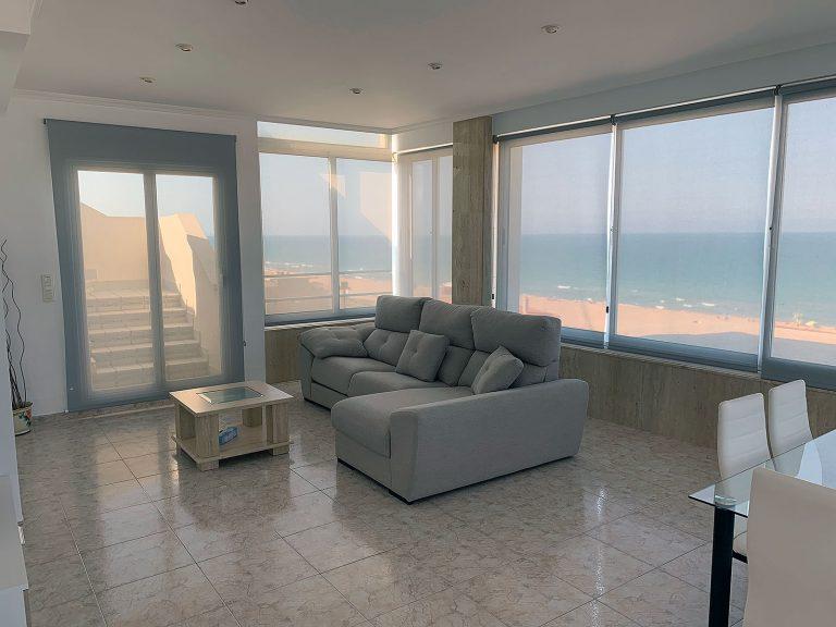 Proyecto 18381 desarrollado por CASANOVA en apartamento de la Playa de Xeraco (Valencia): salón comedor, tapicería, mesa de centro, mesa, sillas, cortinas y decoración.